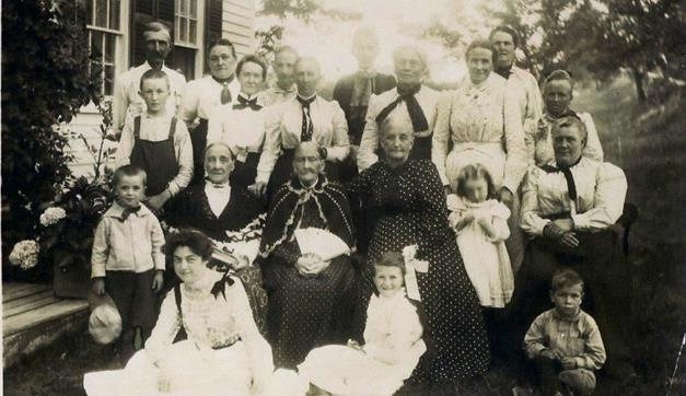 Circa 1900: left side front to back is Russell, Paul Murray, and Edwin Yeaton. Next row is Carrie (sitting), Lydia Ann (wife of Paul Yeaton, Jr.), and Lillian, with the bow. Next to Lydia is her sister, Eliza (wife of Andrew ). Girl in front with the bow in her hair is Donna Yeaton. The lady to the right of Eliza may be her daughter Mary.